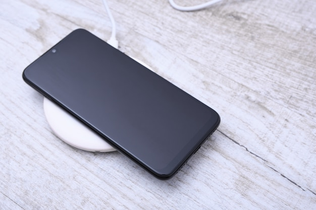 Carga do telefone móvel em um carregador sem fio, conceito de equipamento moderno