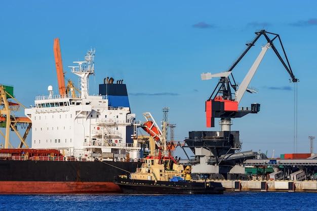 Cargueiro preto atracado no porto com apoio de rebocador