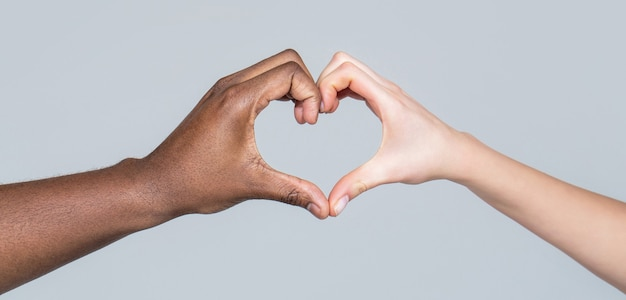 Caridade, amor e diversidade - close up de mãos femininas e masculinas de diferentes cores de pele, fazendo formato de coração pessoas de diferentes cores de pele juntam as mãos, formando um coração em fundo branco.