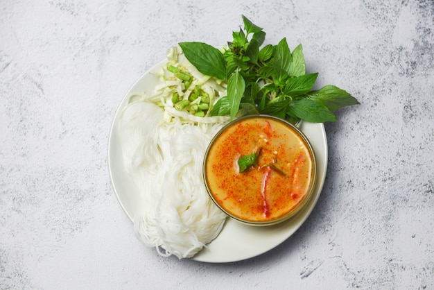 Caril cozinha comida asiática em cima da mesa - comida tailandesa caril sopa tigela com macarrão de arroz tailandês vermicelli ingrediente erva vegetal na chapa branca