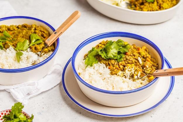 Caril da lentilha com arroz, culinária indiana, tarka dal, fundo branco. comida vegana.