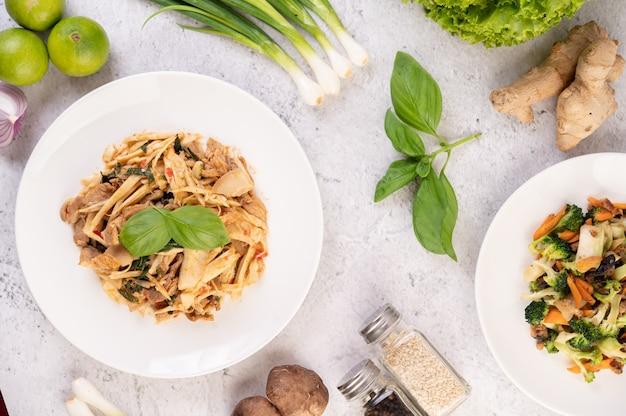 Caril de broto de bambu, adicione a carne de porco em um prato branco.