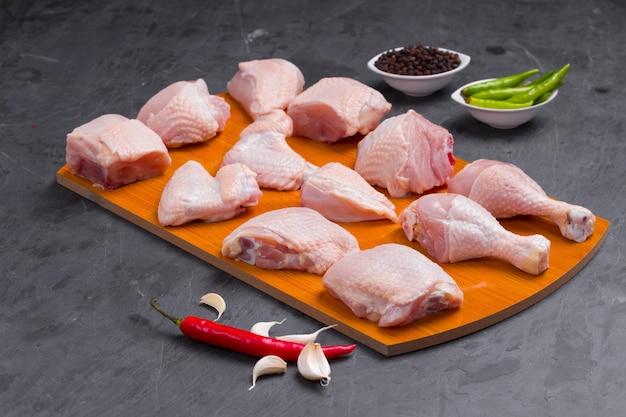 Caril de frango cru cortado com pele disposta em uma placa de madeira