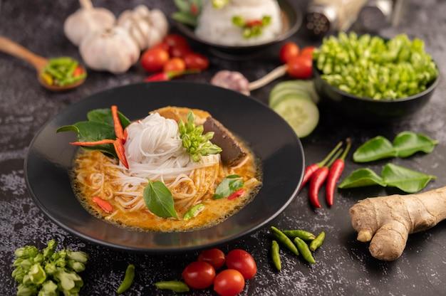 Caril de frango em um copo preto com macarrão de arroz.