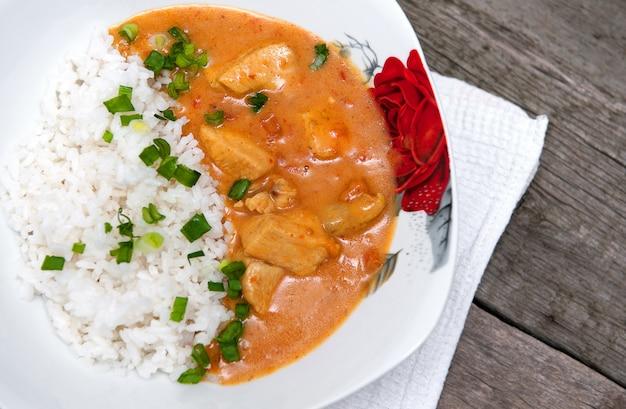 Caril de frango em um prato branco com arroz
