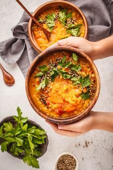 Caril indiano da sopa de lentilha do vegetariano com salsa e sésamo em uma bacia de madeira nas mãos.