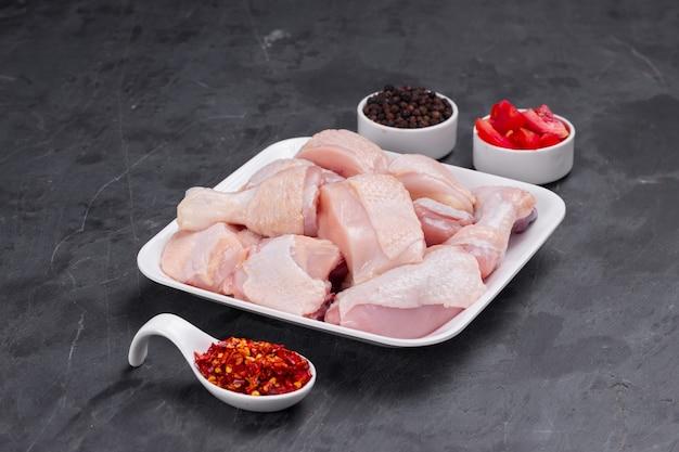 Caril macio de frango cru cortado com a pele disposta em um prato branco