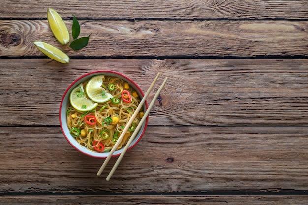 Caril picante de coco com macarrão de arroz e legumes de jardim.