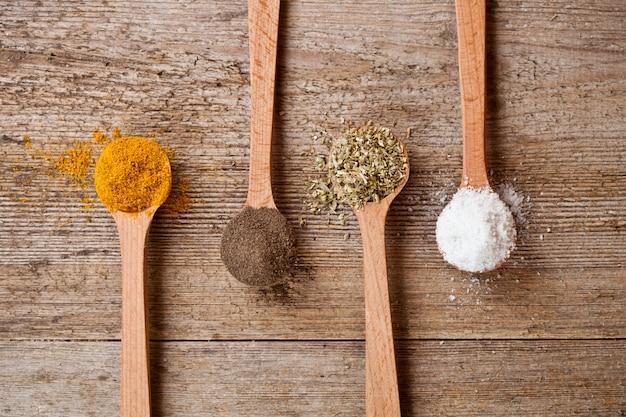 Caril, pimenta, orégano e sal de cozinha em colheres de madeira