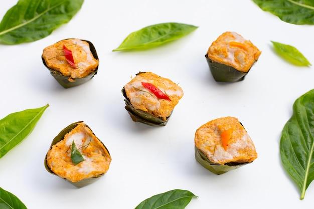 Caril tailandês de peixe escorrido em folhas de bananeira com folhas de noni ou morinda citrifolia na superfície branca