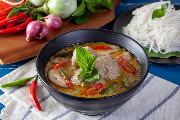 Caril verde com bola de peixe no fundo de madeira, cozinha tailandesa
