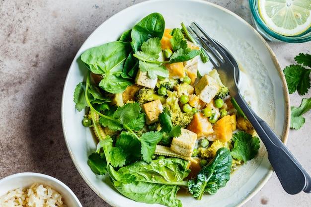Caril verde tailandês do vegetariano com tofu, batata doce, milho e espinafres, vista superior.