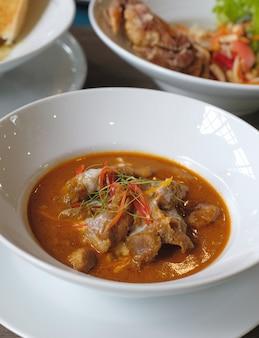Caril vermelho tailandês closeup com costela de porco