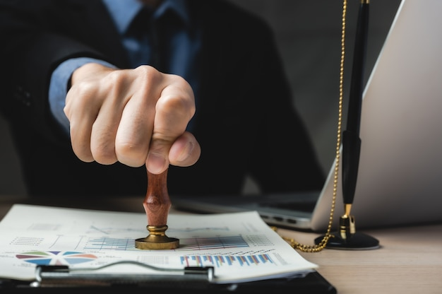 Carimbo da mão da pessoa com carimbo aprovado no documento de marketing empresarial na mesa de um escritório moderno