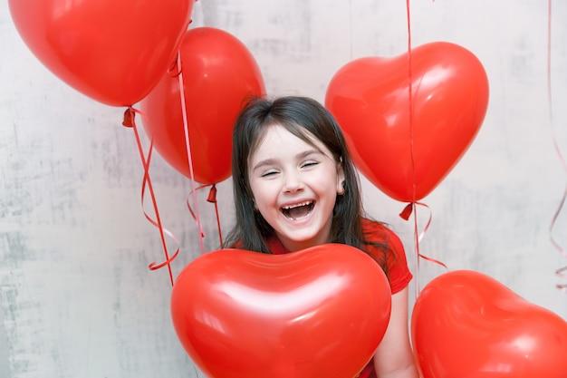 Carinha engraçada da menina rindo close-up entre balões vermelhos em forma de coração