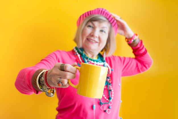 Carinha engraçada de mulher idosa feliz bebendo uma xícara de café ou chá com roupas elegantes