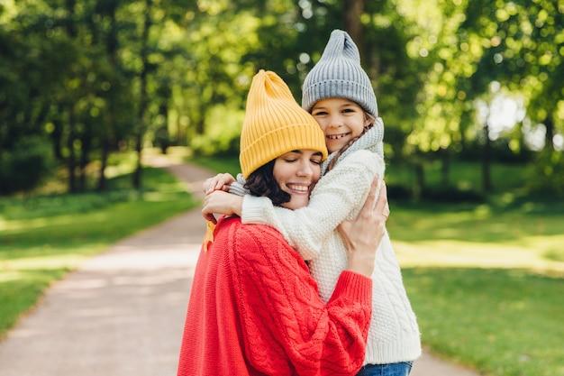 Carinhosa boa aparência jovem mãe abraça sua filha solteira