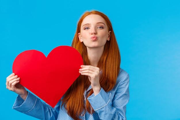 Carinhosa e romântica namorada adolescente fofa segurando cartão de coração vermelho e lábios dobrados