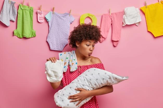 Carinhosa mãe afro-americana olha com amor para o recém-nascido, quer beijar o bebê precioso, segura a fralda, posa