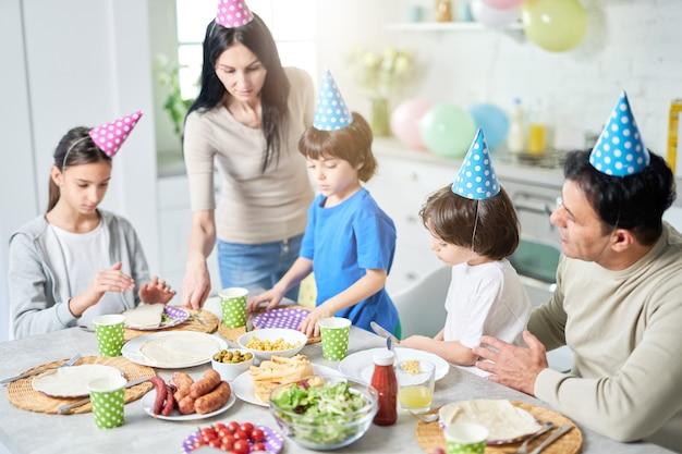 Carinhosa mãe latina de meia-idade servindo sua família enquanto eles jantavam, comemorando o aniversário juntos em casa. paternidade, conceito de celebração. foco seletivo