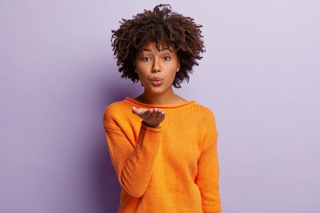 Carinhosa mulher de pele escura com corte de cabelo afro, estica a palma da mão, manda beijo no ar, usa blusão laranja, isolada sobre parede roxa. senhora positiva flerta com namorado, expressa carinho, amor