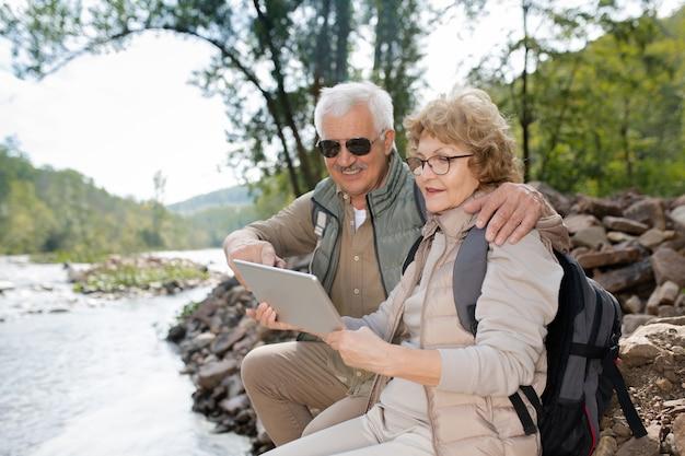 Carinhoso casal de idosos usando roupas esportivas, navegando pelo sistema de navegação na tela do touchpad enquanto está sentado perto da água