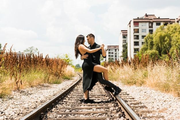Carinhoso casal jovem dançando na estrada de ferro
