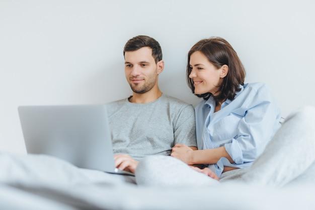 Carinhoso feminino e masculino têm alegria juntos, assistir filme no quarto no computador portátil.