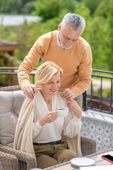 Carinhoso homem de meia-idade, de cabelos grisalhos, cobrindo os ombros de uma bela loira com uma manta