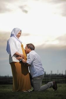 Carinhoso jovem casal muçulmano asiático, marido beijando a barriga da esposa grávida