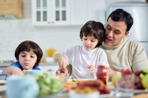 Carinhoso pai latino de meia-idade servindo seu adorável filho, sentado com as crianças na mesa da cozinha, enquanto almoçava em casa. paternidade, conceito de cuidado. foco seletivo