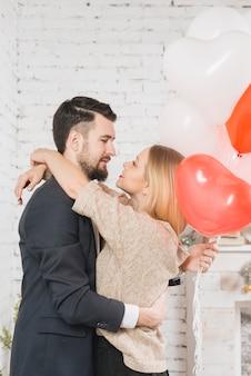 Carinhoso, par, com, balões, em, abraço