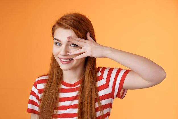Carismática adorável ruiva sortuda fêmea, sorrindo fofa, peek câmera tenro olhar coquete, segurar o rosto da palma da mão, olhar por entre os dedos, ficar fundo laranja otimista, humor alegre