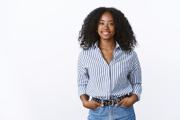 Carismática alegre atraente afro-americana com corte de cabelo encaracolado vestindo uma camisa de mãos dadas, bolsos, confiante, extrovertido, sorrindo, conversando uma conversa agradável, sentindo-se autoconfiante relaxado