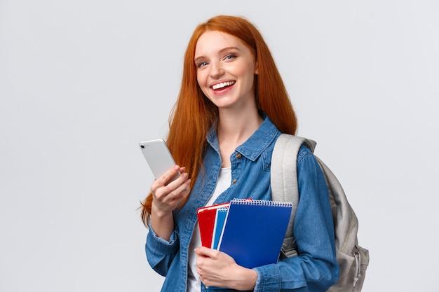 Carismática, feliz sorrindo ruiva adolescente, estudante universitário com mochila