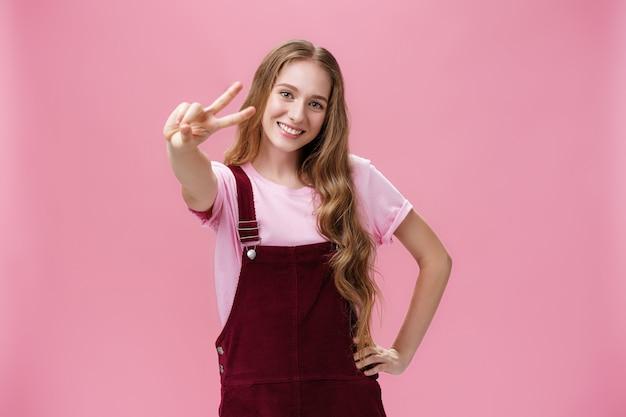 Carismática jovem adolescente de macacão de veludo cotelê posando com alegria e energia contra um fundo rosa, mostrando o símbolo da paz para a câmera, segurando a mão na cintura em pose confiante e sorrindo alegremente.