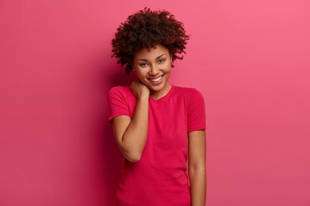 Carismática linda mulher sensual de cabelos cacheados tocando o pescoço, tem um sorriso feliz no rosto, gosta de passar o tempo com pessoas engraçadas, usa camiseta casual, posa sobre parede rosa, tem aparência amigável