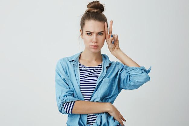 Carismático atraente sexy caucasiano mulher jovem penteado fazendo mal-humorado sério forte forte-rosto mostrando paz, sinal de sorte franzindo a testa, fazendo careta se divertindo, posando