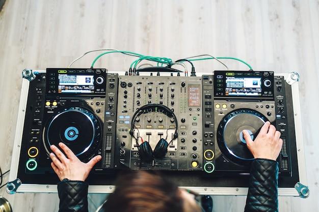 Carismático disc jockey na plataforma giratória. ele toca nos melhores e famosos tocadores de cd da boate durante a festa.