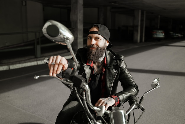 Carismático motociclista em uma motocicleta sorrindo