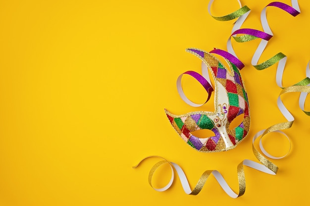 Carnaval festivo e colorido ou máscara de carnaval e acessórios sobre parede amarela. camada plana, vista superior, espaço de cópia