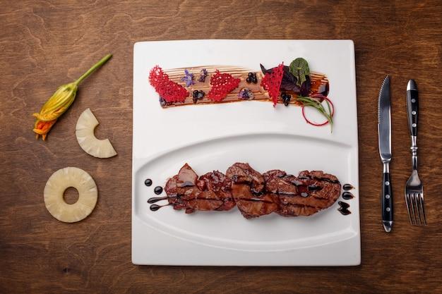 Carne assada com abacaxi em molho balsâmico em uma placa de madeira marrom