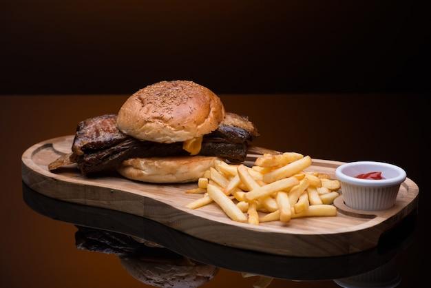 Carne assada com batata frita em bandeja de madeira