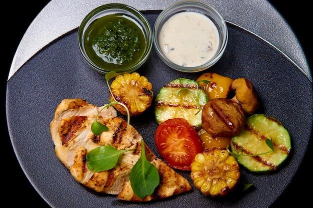 Carne assada com legumes e molho no prato.