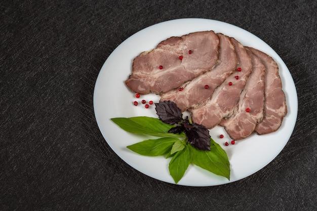 Carne assada cortada em pedaços em um prato branco com manjericão e grãos de pimenta vermelha closeup vista superior em um