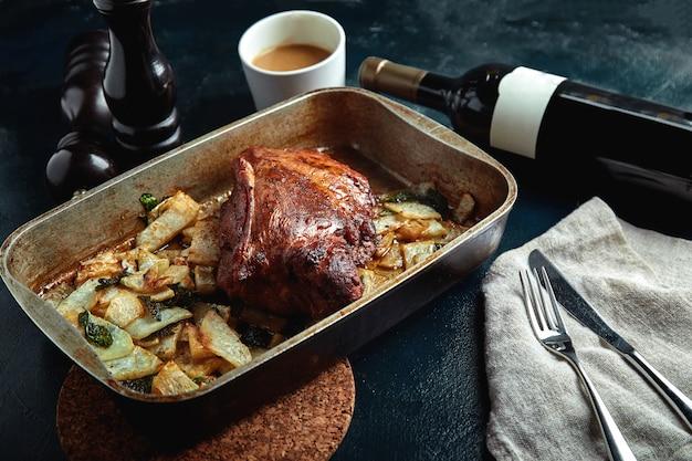 Carne assada e batatas. refeição deliciosa e saudável. grande pedaço de carne assada. comida quente cozida.