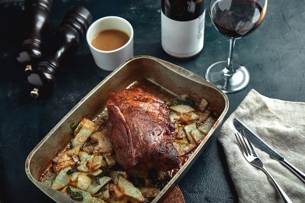 Carne assada e batatas. uma refeição deliciosa e saudável. um pedaço grande de carne assada. comida quente cozida.