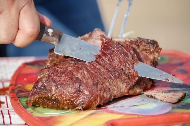 Carne assada e cortada na mesa e fogueira com lenha gaúcha