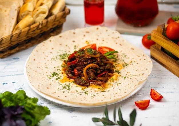 Carne assada e legumes com ervas em um prato branco com pão legumes e copo de vinho