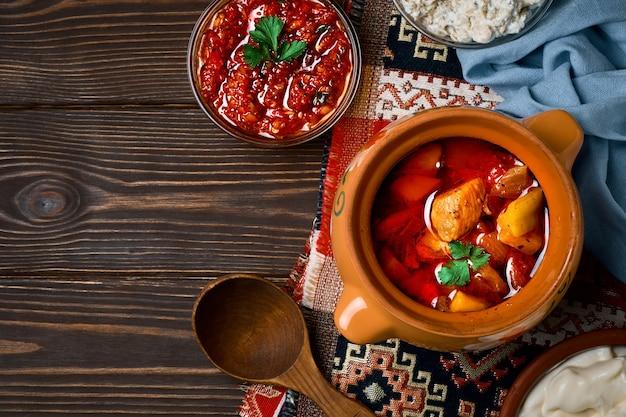 Carne assada em panela de barro, ou travessa tradicional, guisado com legumes e carne cozida no forno. prato de comida turca e balcânica ou oriental, plano com espaço de cópia